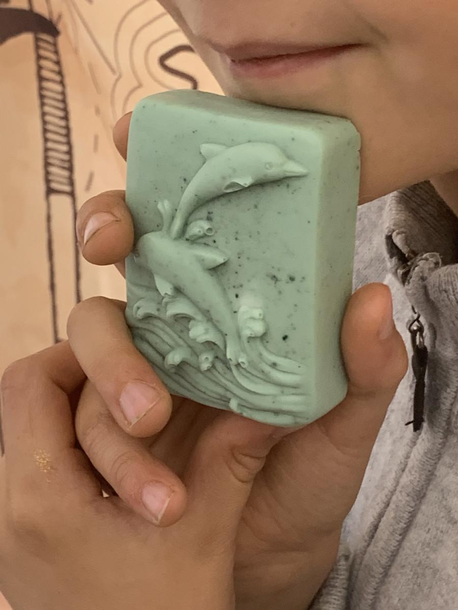 enfant avec son savon naturel personnalisé avec un dauphin